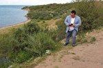 Полномочный представитель правительства в Иссык-Кульской области Асхад Акибаев снимает на телефон мусор на пляжах Тонского района