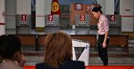 Девушка стоит у электронной урны в избирательном участке. Архивное фото
