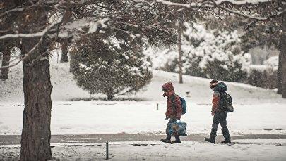 Школьники идут по улице во время снегопада. Архивное фото