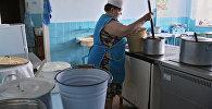 Повар раскладывает обед по группам на кухне. Архивное фото