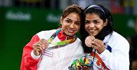Бронзовые призеры соревнований по вольной борьбе среди женщин в весовой категории до 58 кг XXXI летних Олимпийских игр (слева направо): Марва Амри (Тунис), Сакши Малик (Индия) – во время церемонии награждения.