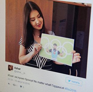 Девушка держит портрет тяжелоатлета Иззата Артыкова, фото со страницы твиттер