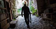Человек с автоматом в Сирии на территории замка Крак Де Шевалье. Архивное фото