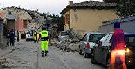 Спасатели рядом с разрушенными домами от сильного землетрясения в городе Аматриче в Италии