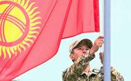 Кыргызстандын желегин илип жаткан аскер кызматкери. Архив