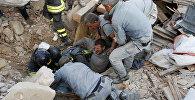 Спасатели помогают пострадавшему в землетрясении в городе Аккумоли в центральной Италии