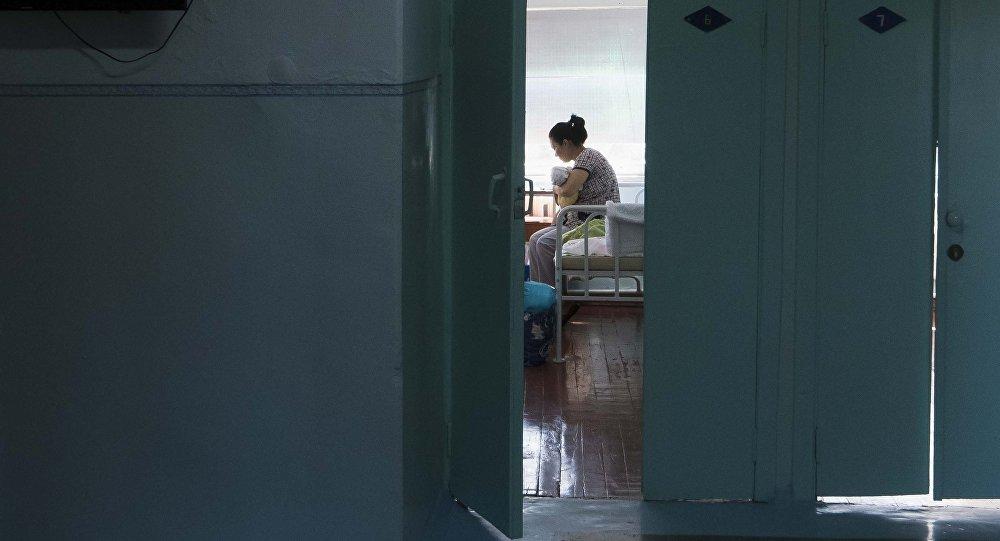 Женщина с новорожденным ребенком в палате родильного дома. Архивное фото
