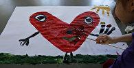 Архивное фото девочки, которая кисточкой рисует сердце