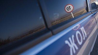 Отражение в машине дорожно-патрульной службы знака ограничения максимальной скорости. Архивное фото