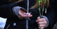 Девушка держит в руках свечи и цветы. Архивное фото