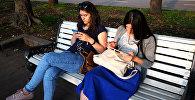 Девушки с телефонами в одном из парков Москвы. Архивное фото