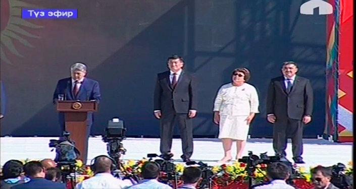 Экс-президент КР Роза Отунбаева покинула сцену на площади Ала-Тоо, не дождавшись окончания поздравительной речи Алмазбека Атамбаева. Снимок с видеотрансляции КТРК во время выступления Алмазбека Атамбаева