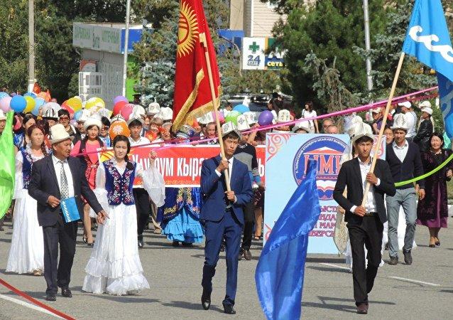 Люди на шествии во время празднования 25-летия независимости Кыргызстана на площади в Караколе