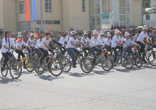 Молодежь на велосипеде на праздновании 25-летия независимости Кыргызстана в Нарыне