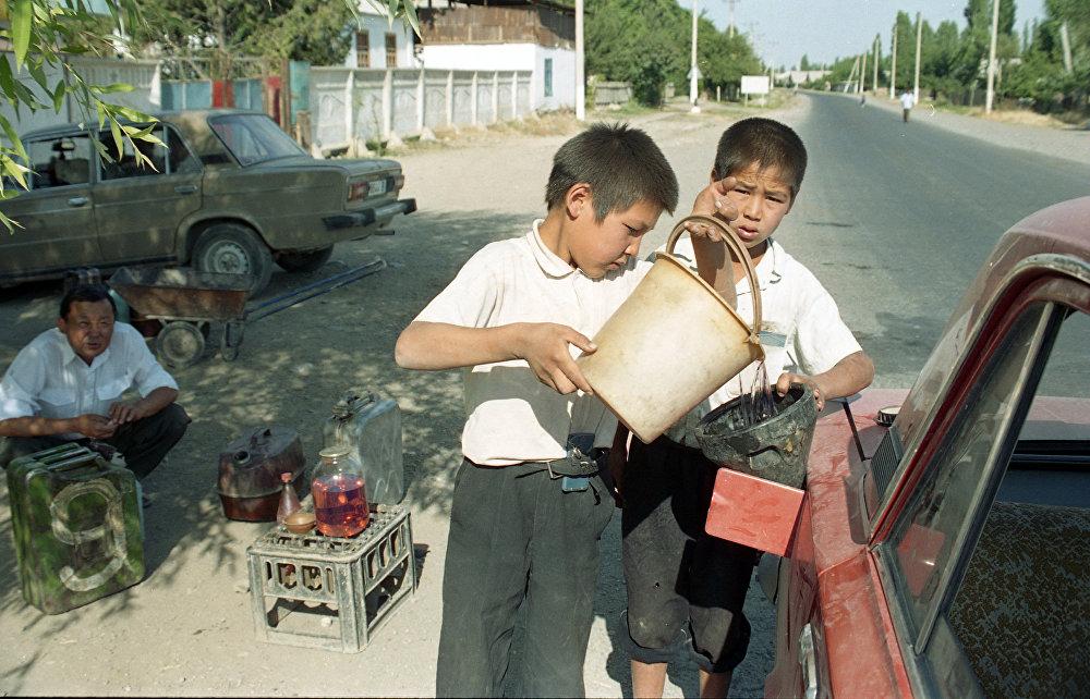 1996-жыл. Жалал-Абадда нефтини кайта иштетүүчү завод курулган. Балдар андан чыккан продукцияларды жолдо сатып жатат