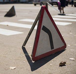 Дорожный указатель Опасный поворот налево на дороге. Архивное фото