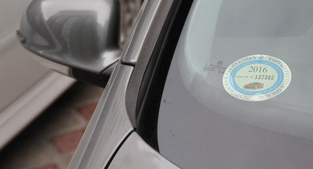 Наклейка об уплате налога на движимое имущество в лобовом стекле автомобиля. Архивное фото
