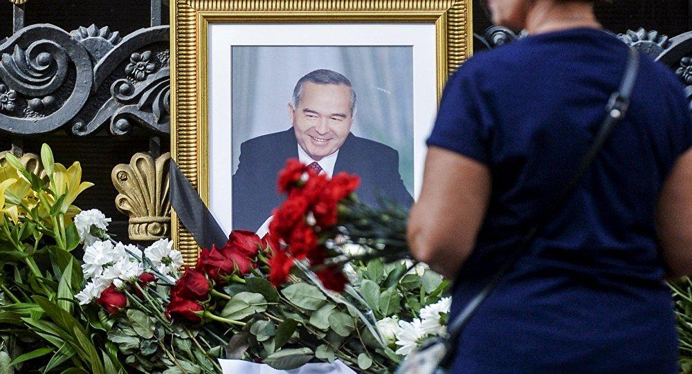 Ислам Каримовдун портретинин жанына койулган гүлдөр.