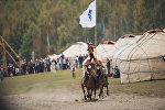 Мальчик на плечах всадников с флагом в рамках Всемирных игр кочевников на джайлоо Кырчын. Архивное фото