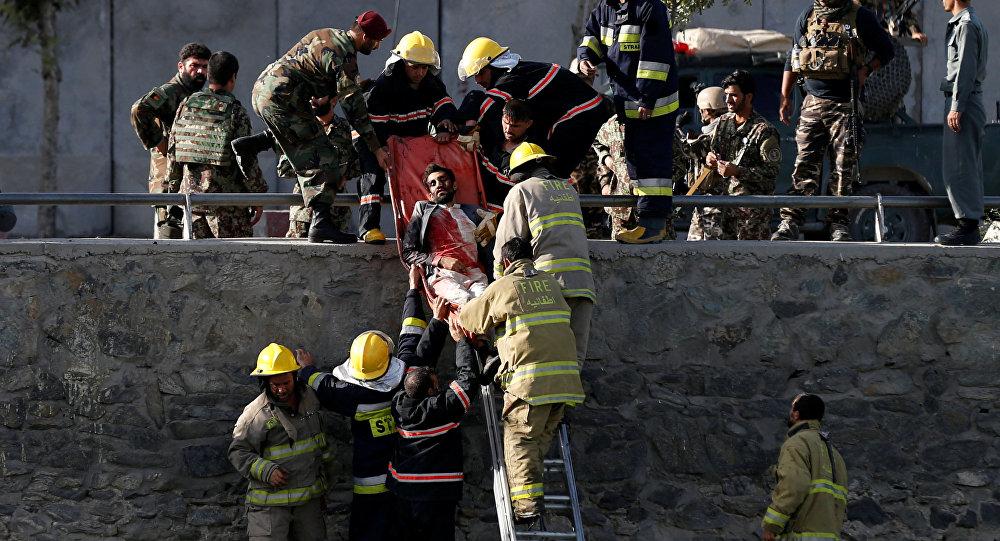 Спасатели и пожарные спускают по лестнице пострадавшего при взрыве в Кабуле