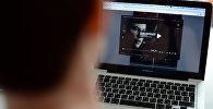 Пользователь смотрит фильм на ноутбуке. Архивное фото