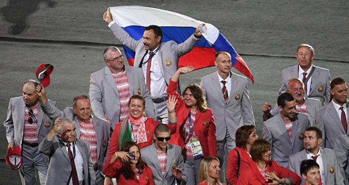 Директор Республиканского центра олимпийской подготовки по легкой атлетике, представитель белорусской делегации Андрей Фомочкин (на дальнем плане) с флагом России во время парада атлетов и членов национальных делегаций на церемонии открытия XV летних Паралимпийских игр 2016 в Рио-де-Жанейро.