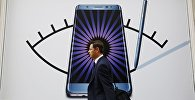 Мужчина проходит мимо объявлений Samsung Galaxy Note 7. Архивное фото
