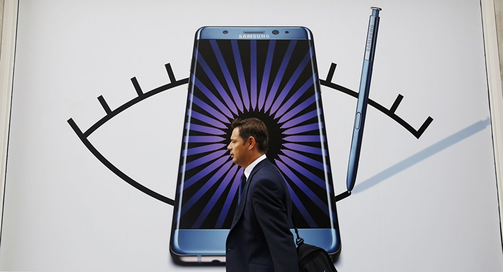 Мужчина проходит мимо объявлений Samsung Galaxy Note 7. Архивное