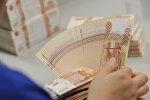 Женщина держит пачку 5000 рублей. Архивное фото