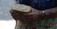 Пожилая женщина держит в руках хлеб. Архивное фото