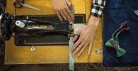 Швейный мастер во время рабочего процесса. Архивное фото