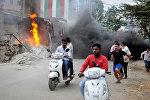 Жители города Бангалор в Индии проходят мимо горящего грузовика во время акция протеста