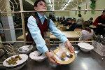 Ученик средней убирает за собой посуду в столовой. Архивное фото