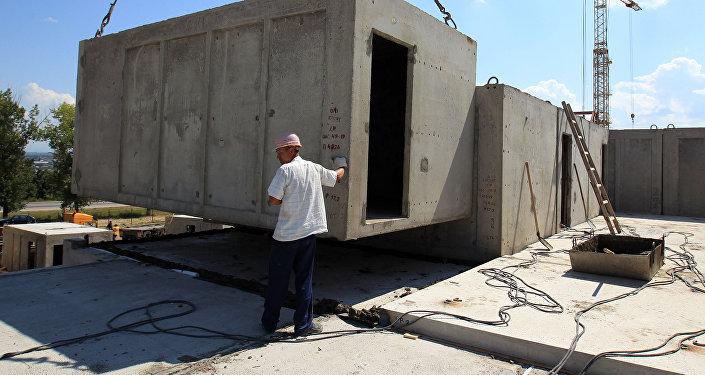 Рабочий контролирует установку бетонной конструкции на строительстве жилого дома. Архивное фото