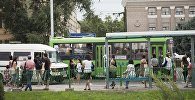 Люди в ожидании общественного траспорта на остановке. Архивное фото