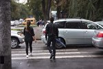 Молодые люди с зонтами переходят дорогу. Архивное фото