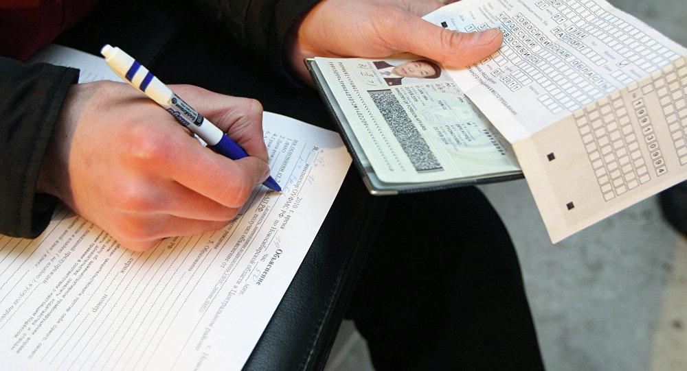 Сотрудник федеральной миграционной службы проводит проверку документов у иностранных рабочих. Архивное фото