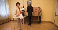 Гражданка России отпускает бюллетень в урну, в посольтве РФ и Кыргызстане в рамках проведения выборов в Государственную Думу России
