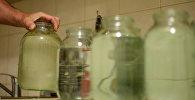 Архивное фото горожанина, который набирает воду в банки