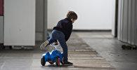Архивное фото ребенка играющего на машинке