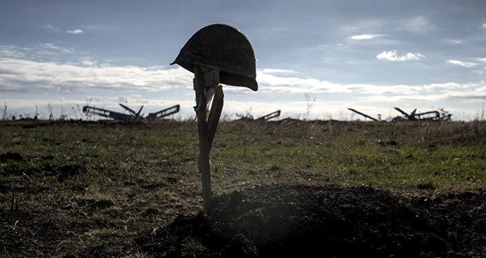 Каска погибшего солдата на могиле. Архивное фото