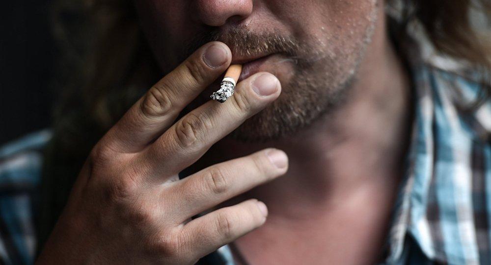 Архивное фото мужчины курящего на улице