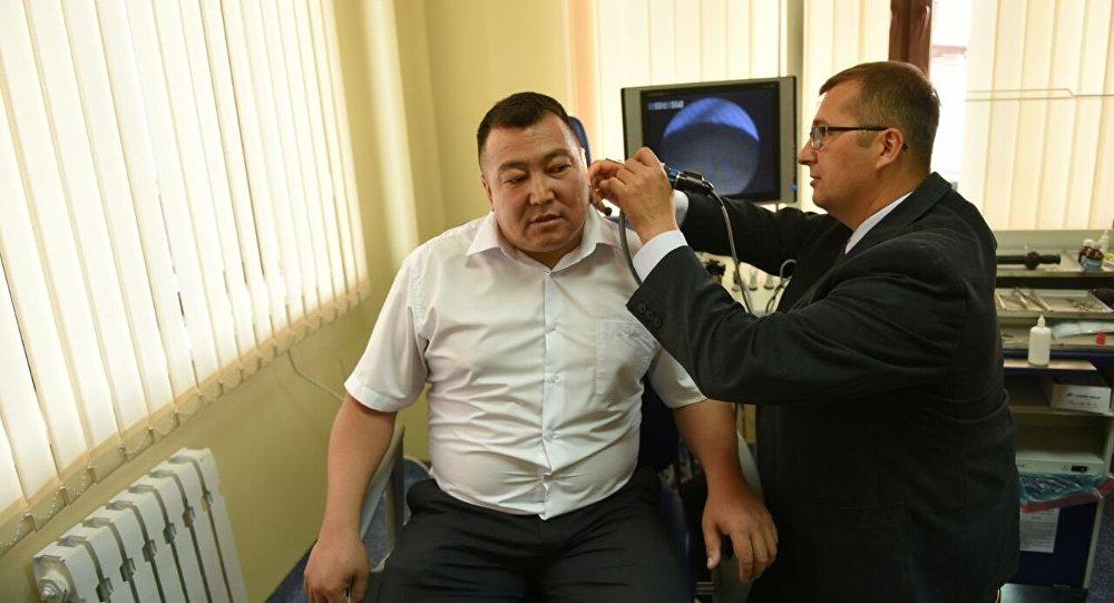 Врач осматривает пациента на новом современном центре слуха и речи в Бишкеке