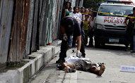 Полиция осматривает тело человека, застреленного во время операции по борьбе с наркоторговлей, 23 сентября 2016