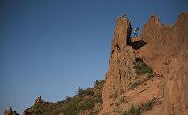 Турист на вершине горного ландшафта в каньоне Сказка в Иссык-Кульской области