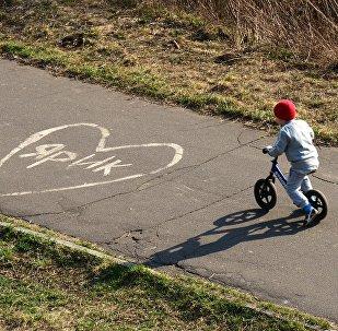 Ребенок катается на велосипеде в парке. Архивное фото