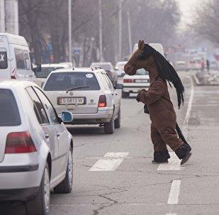 Человек в костюме лошади переходит дорогу на перекрестке в Бишкеке. Архивное фото