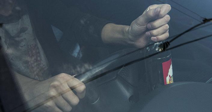 Архивное фото водителя, который держит бутылку водки в руках