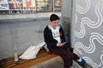 Молодой человек заряжает телефон на остановке общественного транспорта. Архивное фото