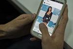 Пользователь смотрит страницу Instagram Ким Кардашян с экрана смартфона. Архивное фото